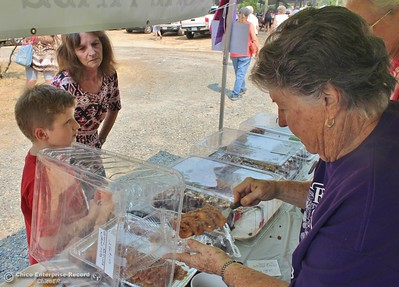 Alice Carlson scoops up some goodied for Travis and grandma Rachelle Scrablin Saturday at the 20th annual Berry Festival at the Berry Creek Grange. (Steve Schoonover -- Enterprise-Record)