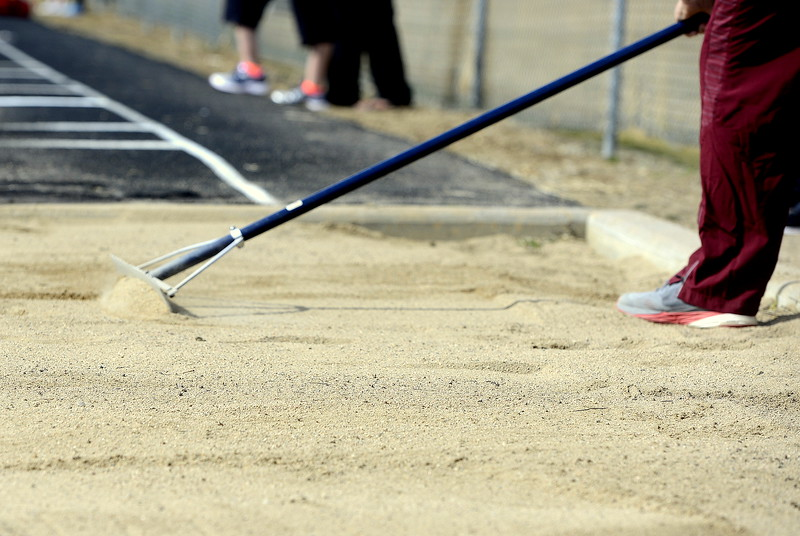 A worker rakes the sand in the triple jump pit at Marr Field to smooth the sand for the next competitor at the Spartan Spike 1 in Berthoud on Thursday. (Mike Brohard/Reporter-Herald)