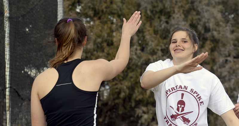 Berthoud's Celsey Selland (facing) gives teammate Casady Berry a high five after Berry threw a personal-best 82-6 in the finals of the discus Thursday at the Spartan Spike 1 at Marr Field. Selland took fifth, Berry eighth. (Mike Brohard/Reporter-Herald)