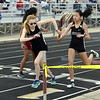 Berthoud's Ellie Sundheim takes the baton from Genevive Babyak in the first exchange of the 3,200-meter relay at the Spartan Spike 1 at Marr Field in Berthoud on Thursday. The Spartans won the race. (Mike Brohard/Reporter-Herald)