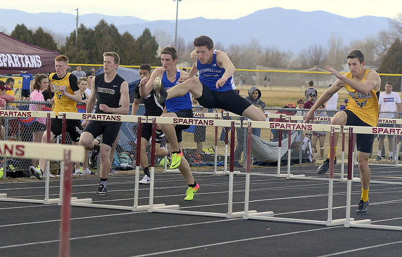 Ben Jackson of Resurrection Christian clears the hurdle in front of teammate Ryan Applebee during the 110-meter hurdles at the Spartan Spike 1 at Marr Field on Thursday. Jackson and Applebee finished 1-2, with Thompson Valley's Nathan Ride (right) in third. (Mike Brohard/Reporter-Herald)