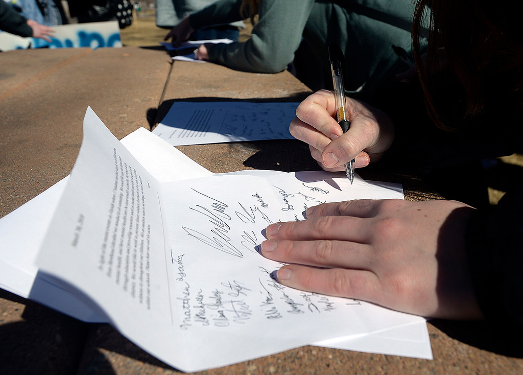. Berthoud High School students sign a letter to Thompson School District officials asking for more mental health resources in schools Tuesday, March 7, 2018, after marching in support of mental health in Berthoud. (Photo by Jenny Sparks/Loveland Reporter-Herald)