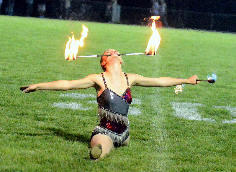 Sarah Kouns performs at halftime Friday night at Marr Field with a pair of flaming batons. (Mike Brohard/Loveland Reporter-Herald)