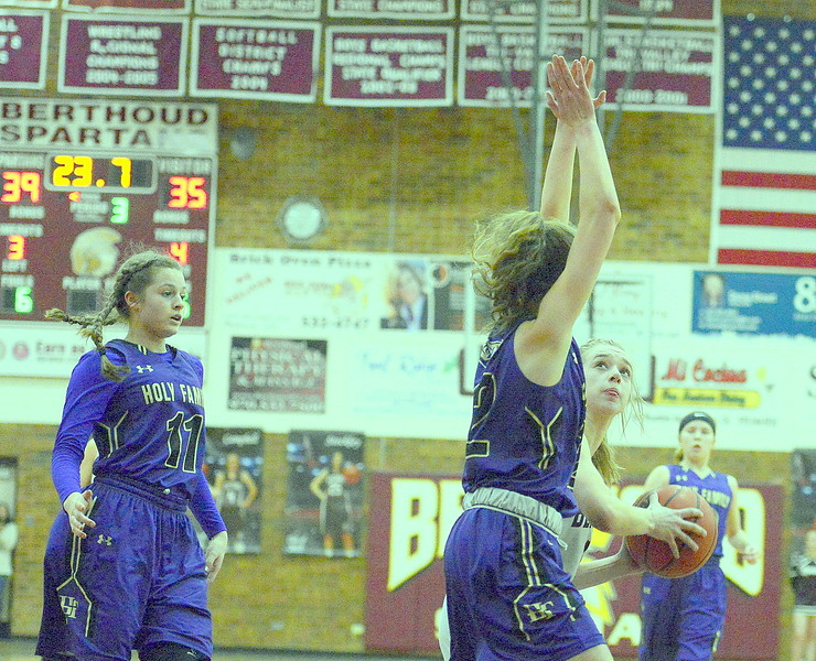 Berthoud's Logan Davidson, right, looks for a shot as Holy Family's  Cecelia Aanerud (32) and Genavieve Gudino (11) defend during Friday's game Tri-Valley Conference game at the BHS gym. The Tigers beat the Spartans 52-50.