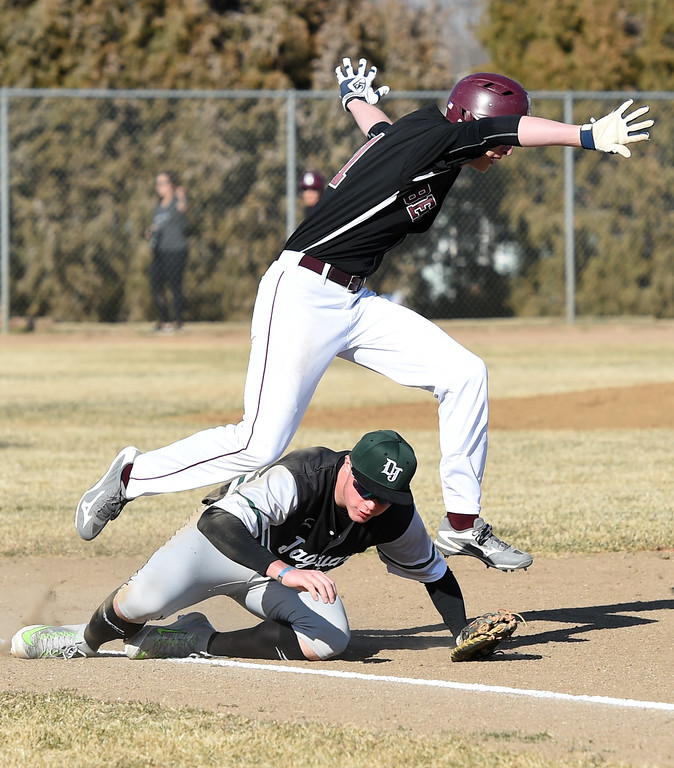 . Berthoud\'s (11) Jordan Rodriguez leaps over D\'Evelyn\'s (28) Evan Willis after making safely to first base during their game Tuesday, March 13, 2018, at Berthoud High School. (Photo by Jenny Sparks/Loveland Reporter-Herald)b 11 d28