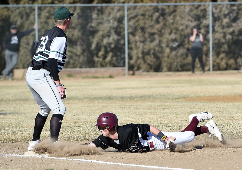 Berthoud's (4) Hunter Pearce slides back in to first base as D'Evelyn's (28) Evan Willis waits for the ball during their game Tuesday, March 13, 2018, at Berthoud High School. (Photo by Jenny Sparks/Loveland Reporter-Herald)