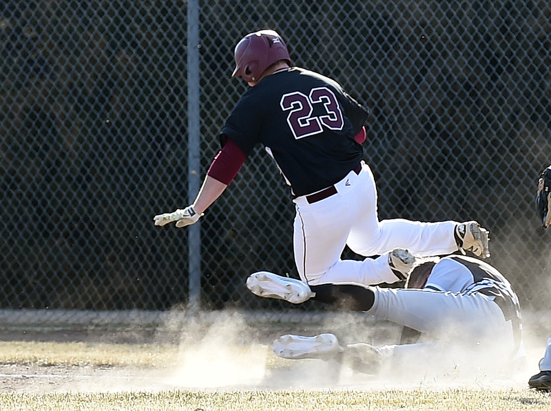 Berthoud's (23) Connor Balliet and D'Evelyn's (28) Evan Willis get tangled up as Balliet tries to get safely to first base during their game Tuesday, March 13, 2018, at Berthoud High School. (Photo by Jenny Sparks/Loveland Reporter-Herald)