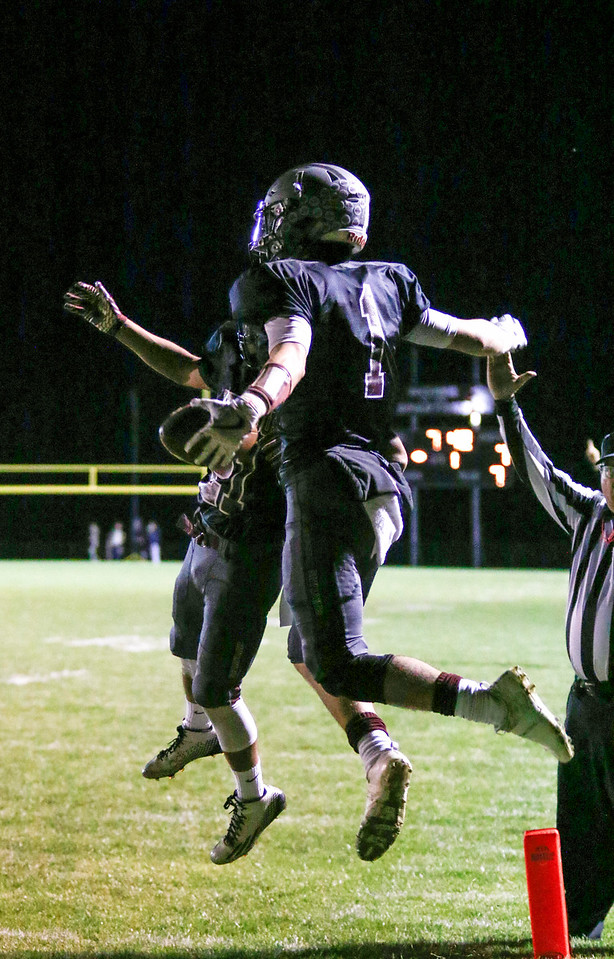 Berthoud's Jacob Lozinski (1) celebrates with Miguel Sarmiento (21) after scoring their first touchdown on Friday, Oct. 6, 2017, at Berthoud High School. (Photo by Lauren Cordova/Loveland Reporter-Herland)