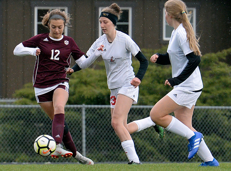 Berthoud's Maddie Barcewski kicks the ball as Loveland's Livia McQuade tries to ge to it during their game Thursday, May 1, 2019, at Berthoud High School.   (Photo by Jenny Sparks/Loveland Reporter-Herald)