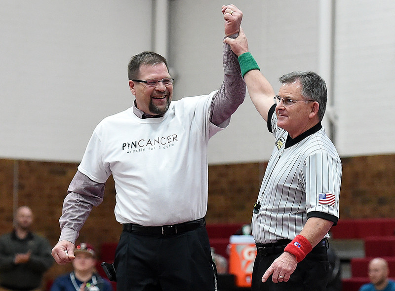 Berthoud High School wrestling coach Scott Pickert, left, is declared the winner by referee Bill Ernst in between matches Thursday, Feb. 2, 2017, as the school takes a moment to thank Pickert for his years of service. (Photo by Jenny Sparks/Loveland Reporter-Herald)