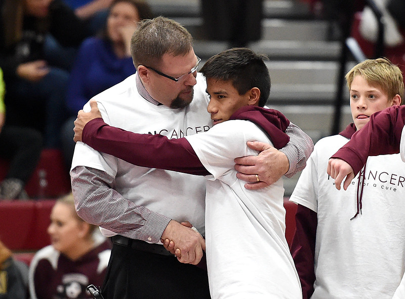 Berthoud High School wrestling coach Scott Pickert, left, hugs wrestler Miguel Sarmiento as he is announced at the start of Pickert's last wrestling meet as their coach Thursday, Feb. 2, 2017. (Photo by Jenny Sparks/Loveland Reporter-Herald)