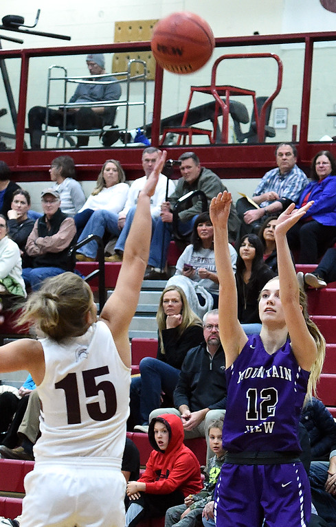 . Mountain View\'s Chloe Miller shoots a three-pointer as Berthoud\'s Addi Spears tries to block during their game Thursday, Dec. 6, 2018, at Berthoud High School.  (Jenny Sparks/Loveland Reporter-Herald)