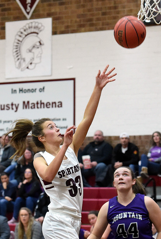 . Berthoud\'s Maddie Barcewski goes up for a shot past Mountain View\'s  Raleigh Basart during their game Thursday, Dec. 6, 2018, at Berthoud High School.  (Jenny Sparks/Loveland Reporter-Herald)