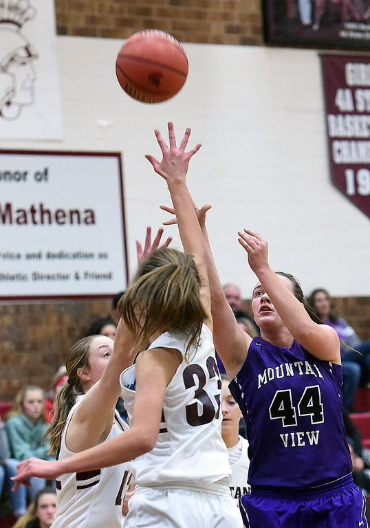 . Mountain View\'s Raleigh Basart goes up for a shot as Berthoud\'s Maddie Barcewski tries to block during their game Thursday, Dec. 6, 2018, at Berthoud High School.  (Jenny Sparks/Loveland Reporter-Herald)