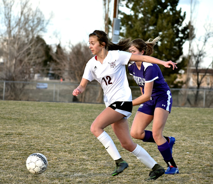 Berthoud's (12, center) Maddie Barcewski goes for the goal as Mountain View's (13) Calli Wilson runs after to steal the ball during their game on Friday, March 23, 2018 at Berthoud High School in Berthoud. Photo by Thieng Mai/Loveland Reporter-Herald.