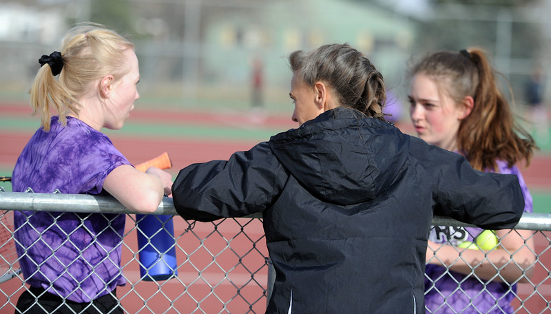 Coach Patti Lang talks to Mandy McNulty, left, and Hope Brown during the No. 1 doubles match at BHS courts on Thursday, March 28. Berthoud won 7-0. (Colin Barnard/Loveland Reporter-Herald)