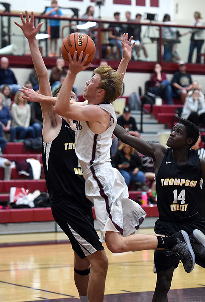 Berthoud's Curtis Peacock goes up for a shot as Thompson Valley's John Barnhill tries to block during their game Thursday, Dec. 20, 2018, at Berthoud High School. (Photo by Jenny Sparks/Loveland Reporter-Herald)