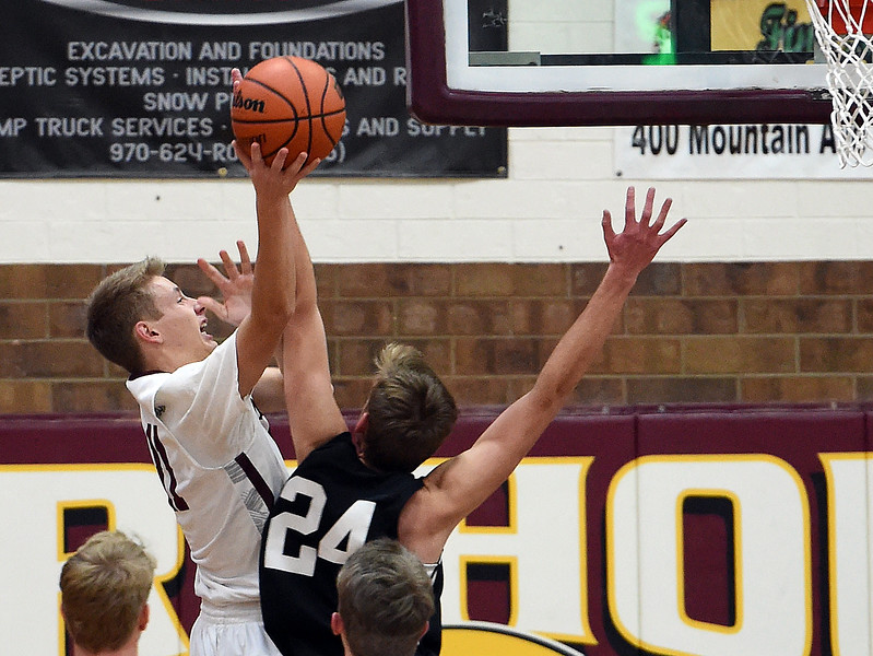 Berthoud's Brent Hoogland goes up for a shot as Thompson Valley's Jacob Brouwer tries to block during their game Thursday, Dec. 20, 2018, at Berthoud High School. (Photo by Jenny Sparks/Loveland Reporter-Herald)