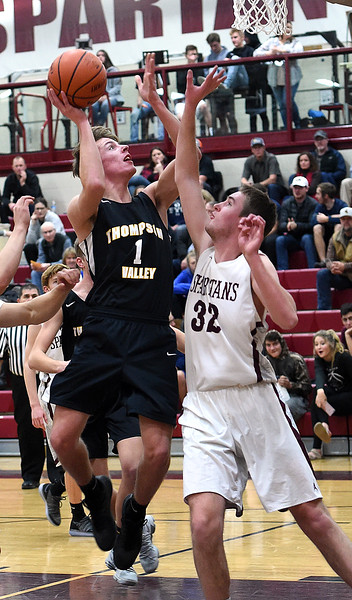 Thompson Valley's Trey Kreikemier goes up for a shot as Berthoud's Rowan Carr tries to block during their game Thursday, Dec. 20, 2018, at Berthoud High School. (Photo by Jenny Sparks/LOveland Reporter-Herald)