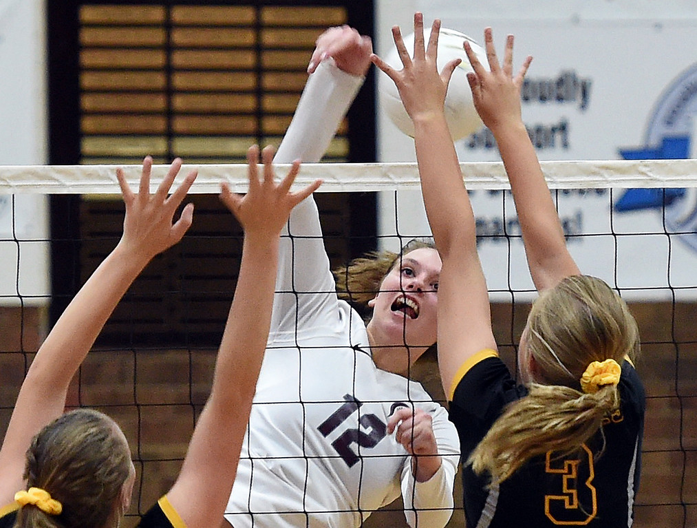 . Berthoud\'s (12) Teagan Holmes spikes the ball as Thompson Valley\'s (3) Sydney Laws tries to block during their game Monday, Aug. 27, 2018, at Berthoud High School. (Photo by Jenny Sparks/Loveland Reporter-Herald)