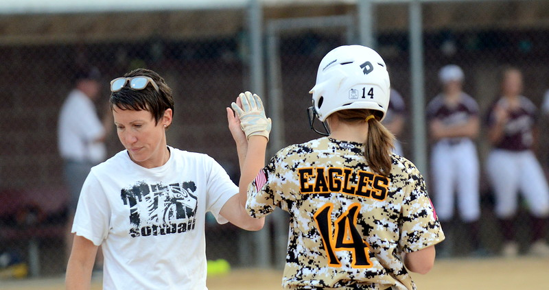 Thompson Valley's Autumn Porter gets a high-five from first-base coach Amanda Rutherford after a first-inning single in Monday's game with Berthoud. (Mike Brohard/Loveland Reporter-Herald)
