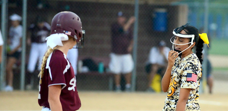 Thompson Valley first baseman Sierra Ortiz chats with Berthoud's Carly Rafferty during Monday's game at Bein Park. (Mike Brohard/Loveland Reporter-Herald)