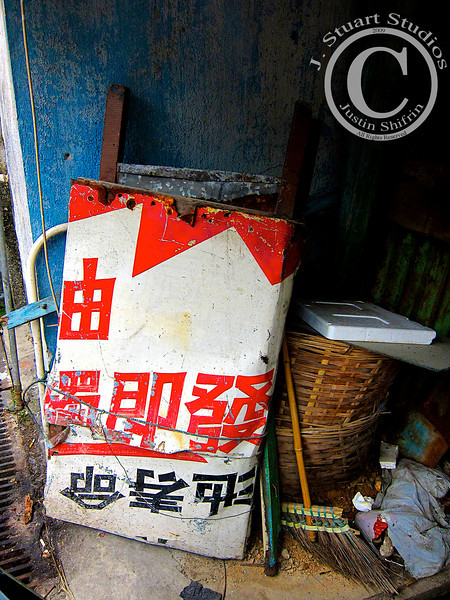 Back-alley Storage<br /> <br /> Shanghai, China is a bustling metropolis that is ever-growing taller and wider.  Leaving the fast-paced urban center for rural back-alleys brought me to this streetscape.<br /> <br /> In a small abandoned hut in the middle of a village sat this trash pile.  The varied debris made for an interesting image.
