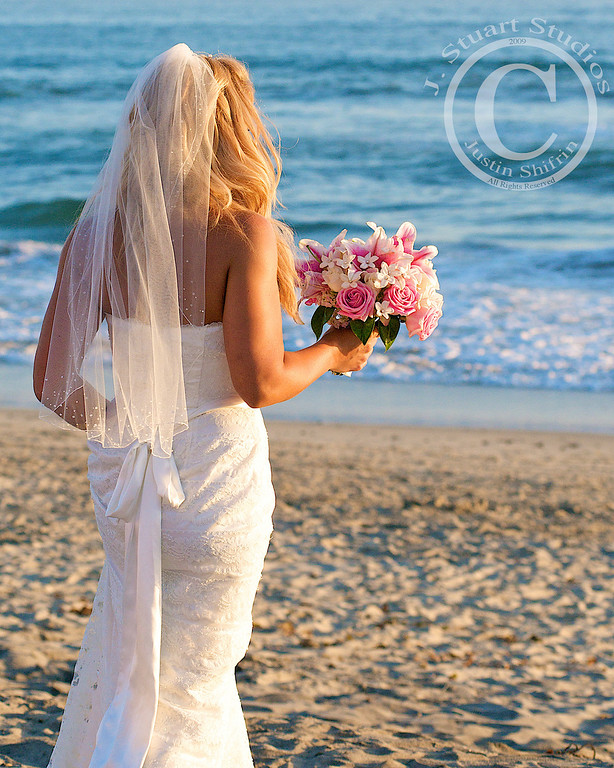Seascape Bridal  This beach bride might not be looking at the camera for this photograph, but the scene perfectly captured the mood of the day's festivities.  As she walked from the altar into the warm sunlight, her skin radiated as she journeyed to the surf for photographs with her new husband, family, and friends.