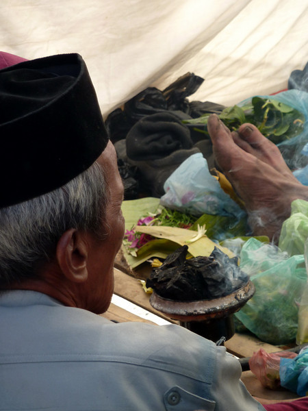 A priest stationed at the foot of Mt Bromo blesses all sacrificial items prior to ascent.