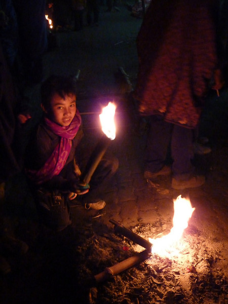 An apprentice assists with the preparation of the torches.