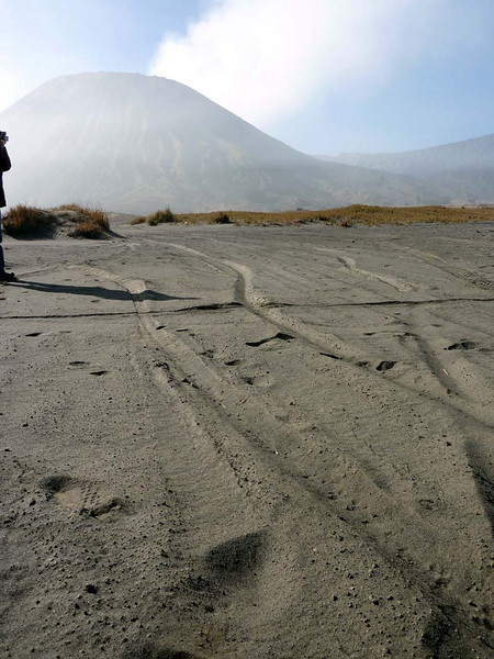 """Motorcycle tracks across the great """"Sand Sea' with Mt Batok in the background."""