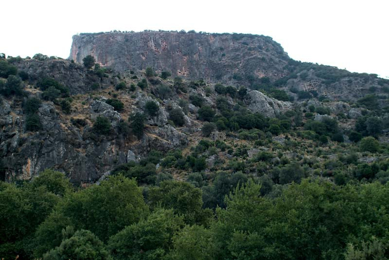 Distant view of the cliffside rock cut tombs in Pinara, along the Lycian Way, Turkey