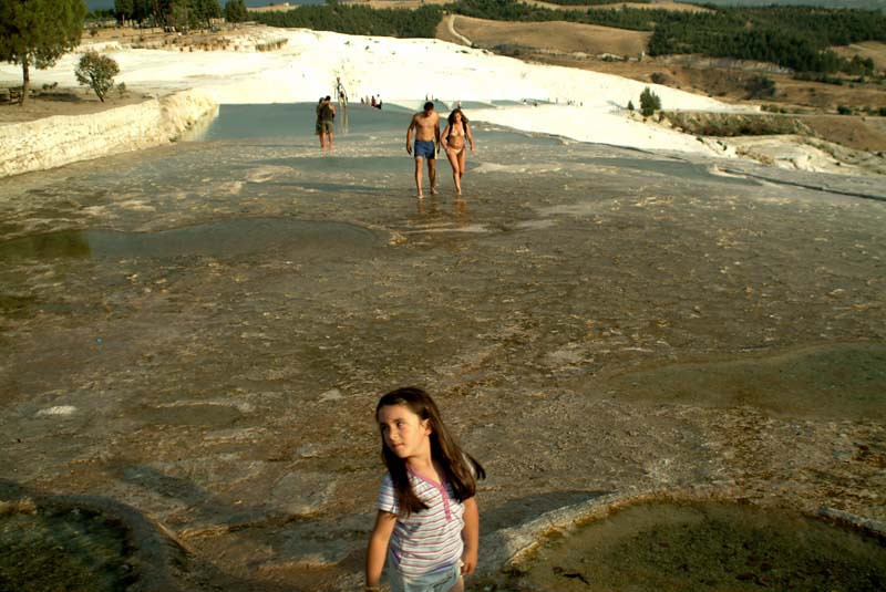 Tourists idly playing in the calcium terraced pools of Paumukkale in central Turkey.