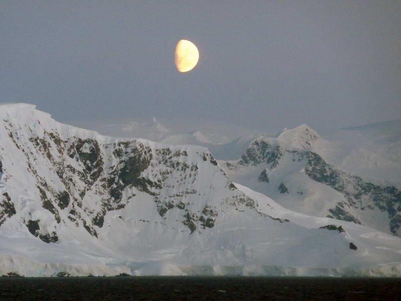 Half moon rising over the mainland in the Gerlache Strait, Antarctic peninsula