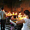 Lighting candles in an ancient mountaintop stone church in rural Armenia.
