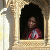 Maudlin retailer peers out from Jaiselmer's most famous house in Rajastan India.
