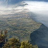 The morning mist streams over the rim ridge of the great Tengger calder near Mt Bromo, East Java Indonesia.