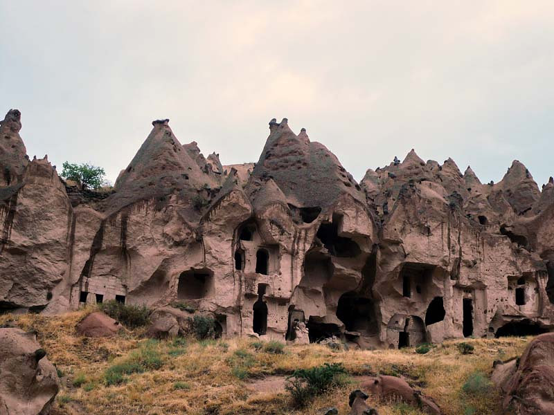 Rough hewn chambers perforate the rock cliff faces in the Zelve open air museum in Kapydokia, Turkey.