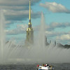 Celebratory water jets in the harbour with a spire of the Peter & Paul Fortess in the background, during Navy Day in St Petersburg, Russia.