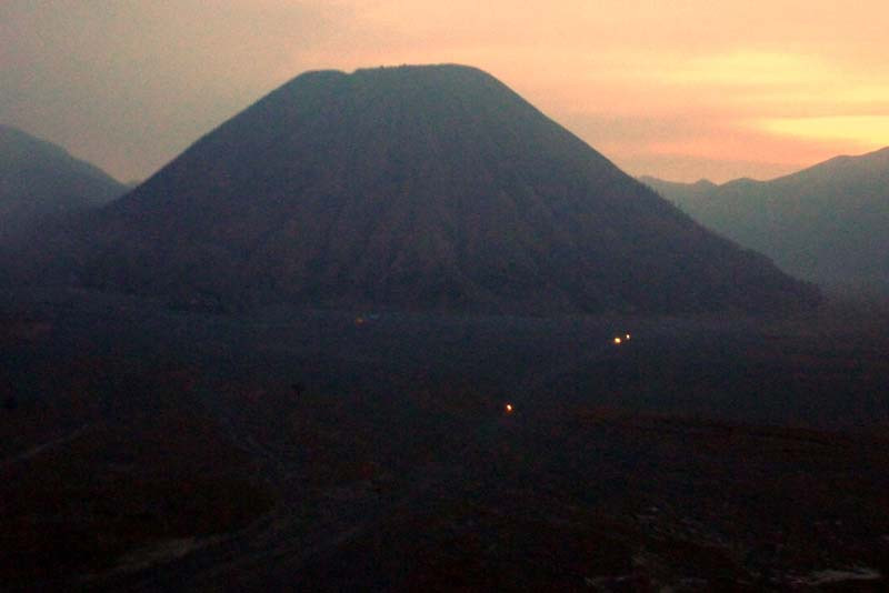 """The headlights of jeeps traversing the floor of the """"Sand Sea"""" in the shadow of Mt Bromo (Batok), just before dawn on Yadnya Kasada."""