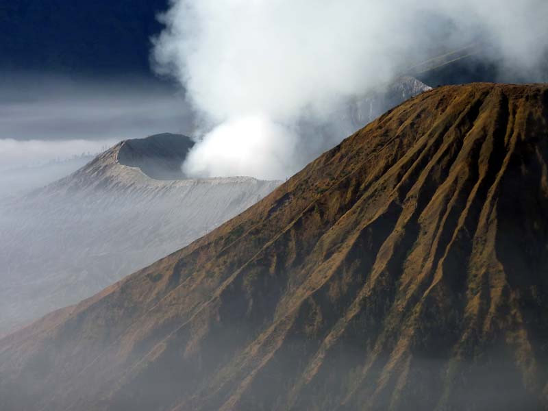 Mt Batok with the gray rim of Mt Bromo peeking out from behind. East Java Indonesia.