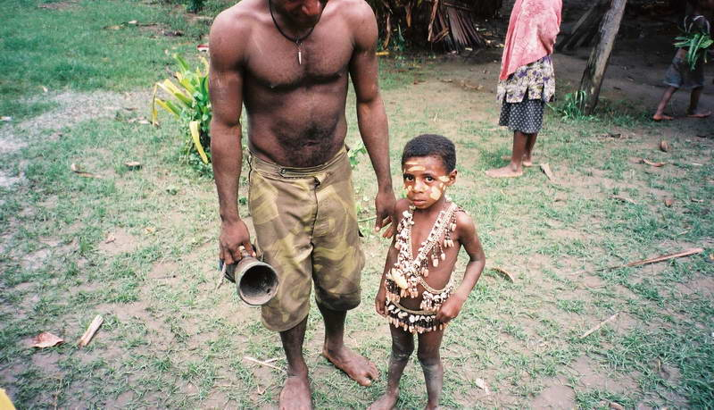 Father and son at a mask dance on the upper Sepik river, Papua New Guinea.