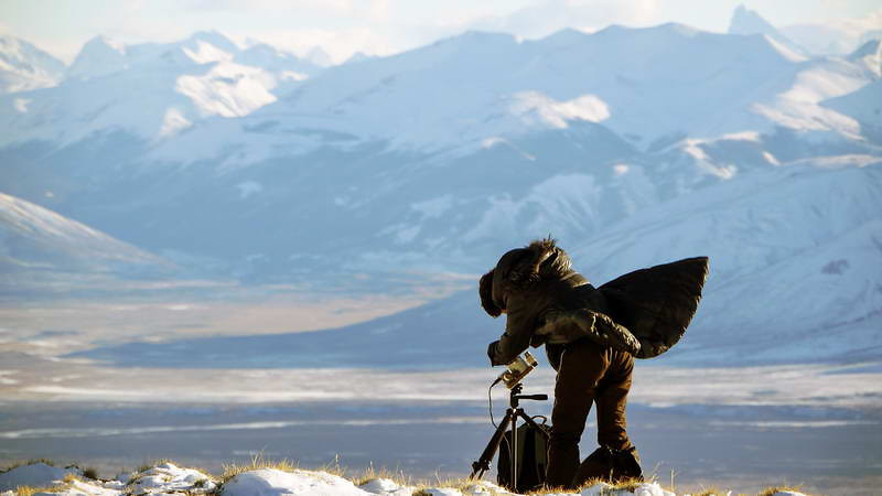 A Japanese woman sets up in fierce winds, for the total solar eclipse of 11 July 2010, atop the Cerro Huyliche plateau in Patagonia, Argentina
