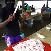 A talented fish butcher slices up the day's catch in a seaside wet market near Nouakchott, Mauritania.