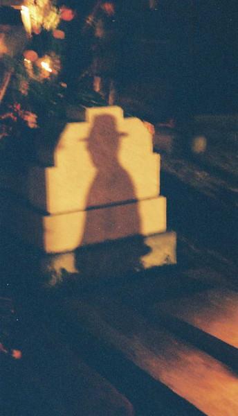 Shadow of Gerardo on a tombstone in the cemetery on Dia Del Muertos in Oaxaca Mexico.