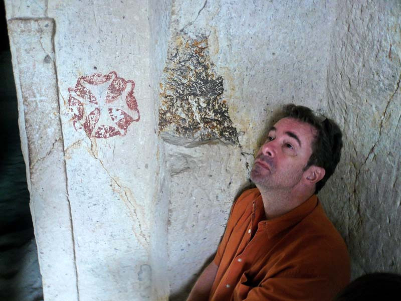 Flip gazes idly at details in the cave chambers whilst an ancient Byzantine zinco motif lurks nearby, in the Goreme open air museum in Kapydokia Turkey.