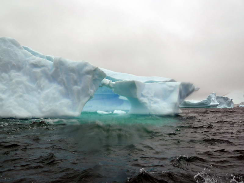 """Natural arch in the """"Icebergs Graveyard"""" in the Penola Strait near Booth Island, Antarctic peninsula"""