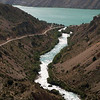 A river runs down from the mountains to a high alpine lake near Penzjikent, Tajikistan.