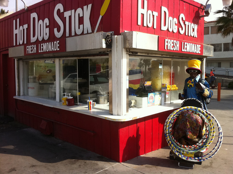 "The ""Hula Hoop Guy"" takes a break at ""Hot Dog Stick"" at the Santa Monica Pier"