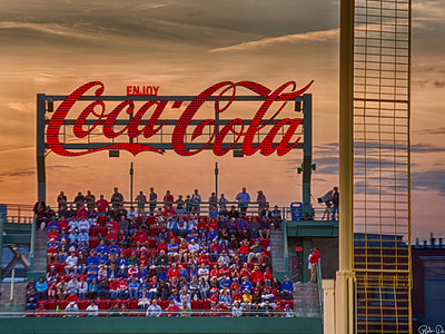 Coca Cola at Fenway | Ahh summer.  This image was created while watching the Red Sox play baseball against the Texas Rangers in June 2013. It is always an enjoyable evening and nothing says summer better than Fenway Park, Coca Cola and Baseball. After the sun had set a golden / orange glow came across the sky. The Soxs were off their game this night and would eventually loose this game.I captured this image using Pesky's pole to frame the image and help identify the location. The bleachers above the Green Monster, shows a very intense crowd watching the game. The sky is the icing on the cake.  My goal was to show the excitement of the evening and found the audience more interesting than the players.  In framing, I needed to keep the camera man in frame.  I also wanted the audience to not be recognizable as individuals but as a crowd.  Looking closely however, you can see many stories.This image was captured using HDR techniques, 5 images at f 8. It was a hand held shot at 200mm. The HDR image was created using NIK tools.